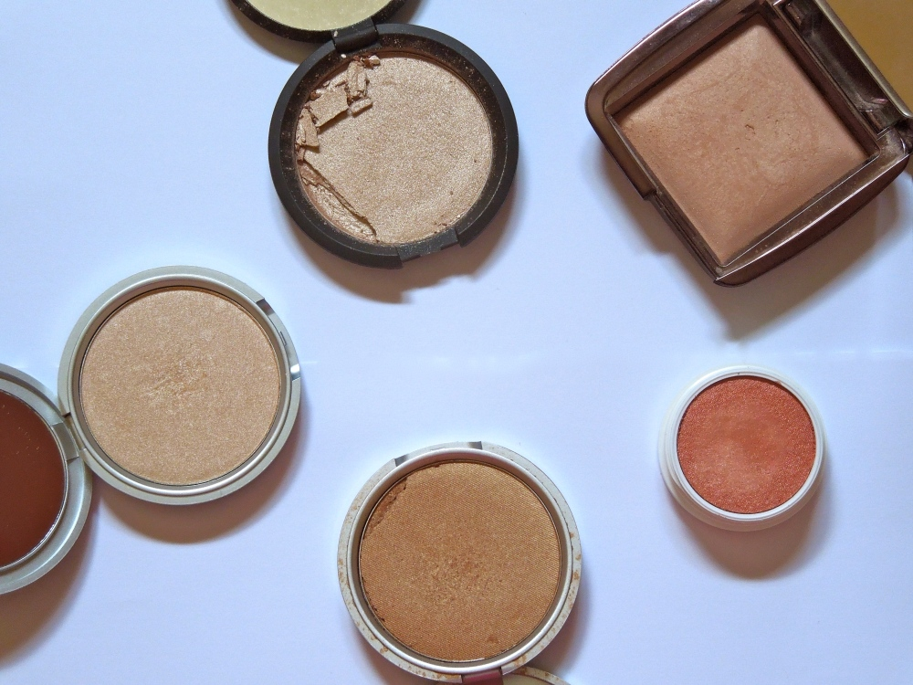 Clockwise from the top: Becca Shimmering Skin Perfector Pressed in Opal, Hourglass Ambient Lighting Powder in Radiant Light, Colourpop Highlighter in Most Necessary, The Balm's Betty Lou-Manizer, and The Balm's Mary Lou-manizer